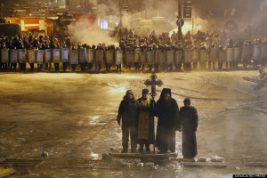 Orthodox priests pray as they stand between pro-European Union activists and police lines in central Kiev, Ukraine, 2014. (Sergei Grits)